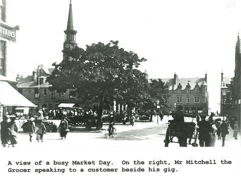 A busy market day in the Square. On the right Mr. Mitchell the grocer is speaking to a customer beside his gig.