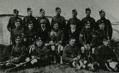 A team of soldiers in highland dress with a cup