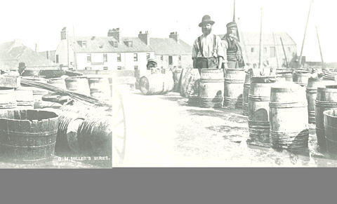 Men working with the barrels at the harbour.