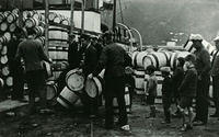 A group of men and boys loading barrels onto a boat in the harbour