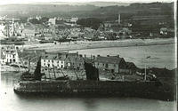 A view from Downies Point of boats at the north pier at the harbour with Stonehaven beach and new town beyond - before The Bay Hotel was built