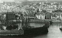 A view from Downie Point of fishing boats in Stonehaven harbour with the new town in the background. Viewmount can be seen top left, and Fetteresso Church top right. The tannery buildings with two chimneys is on the right