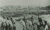 Crowds on the Bridge of Cowie watching soldiers on horseback in the water. Looking towards Megray.