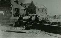 Some fishermen sitting on the harbour wall, with the Tolbooth in the background.