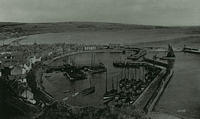 A view of fishing boats in the harbour from Bervie Braes with the beach extending into the distance.