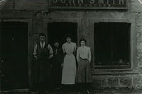 A family standing outside the shop of John Smith, Fishmanger