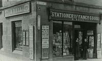 The shop of M. Bell, Stationery and Fancy Goods at 1  Market Square. Bill boards tell of the sinking of the Titanic (1912) and there are displays of postcards and a thermometer on the walls.