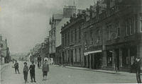 A view north along Allardice Street. The Town Hall with its gas lamps outside can be seen on the right hand side