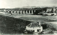 Glenury.  The Glenury viaduct  runs above Minerwell Croft and the playing fields can be seen in front. Glenury Distillery is on the right and a cottage in the foreground.
