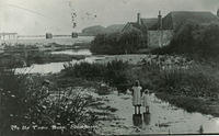 Two children standing in the Cowie burn looking towards the sea where bathing huts can be seen, and Downie Point is in the distance.