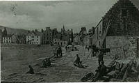 People at the harbour where the tide is out. The Tolbooth is on the right.