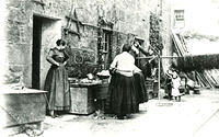 Women and children outside their houses in the Old Town. Fishing lines are hung on a pole.