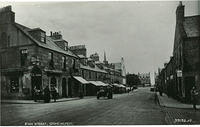 Evan Street looking east from the junction with Ann Street.  The trees in the centre mark the side of Market Square.Clarks - Silversmith, optician, watchmaker & jeweller is on the corner.