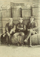 Three men sitting on barrels