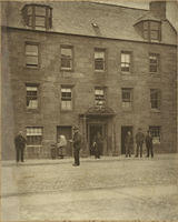 Some people standing outside Peter Christian's House in the High Street - once used for Episcopal Services.