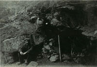 A man sitting next to a cave