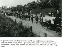 Boy scouts procession with an ambulance carriage