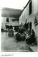 Women and children shelling mussels in Castle Street in the Old Town