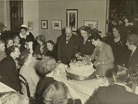 A celebration - people gathered round a special cake.